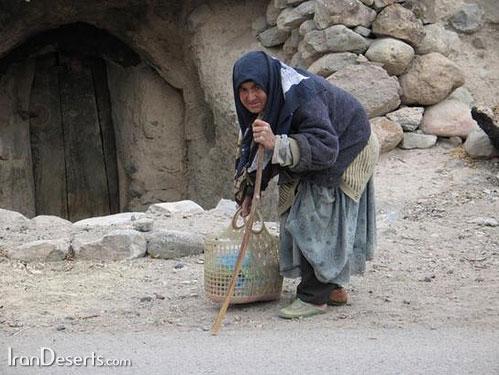 پیر زن میمندی جلو درب منزل مسکونی خود ایستاده